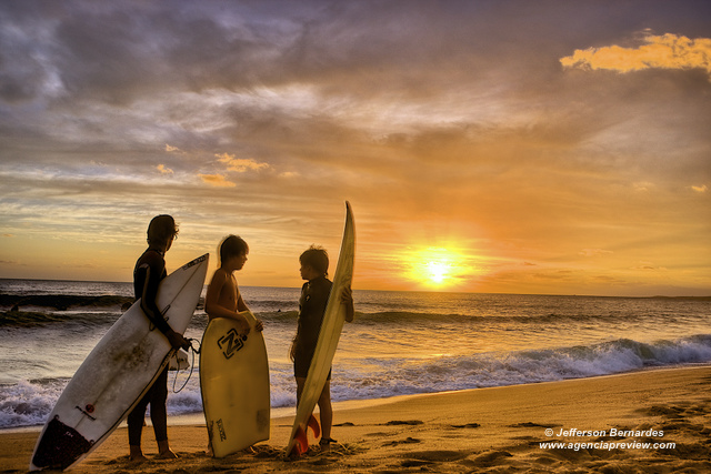 Surfistas ao pôr-do-sol
